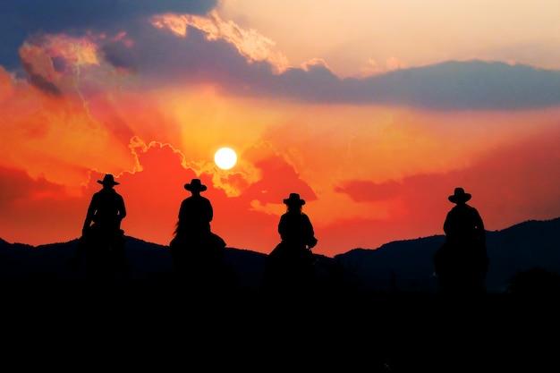 Ковбой на лошадях с видом на горы и закат небо.