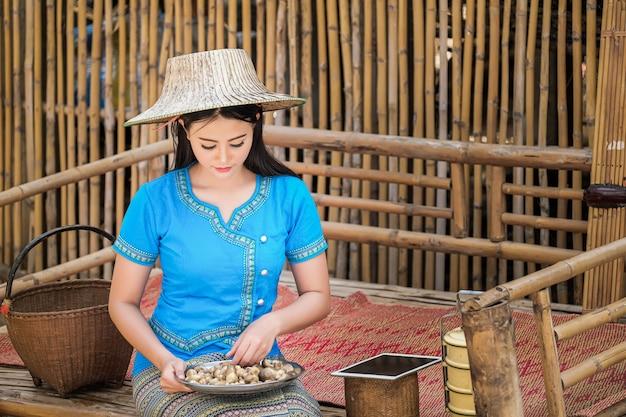 青い伝統的なタイ風のドレスを着た少女は、顧客に注文を送るためにキノコを集めています。