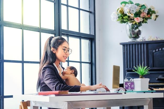 ビジネスで働いて、家で子供を育てるアジアの女性