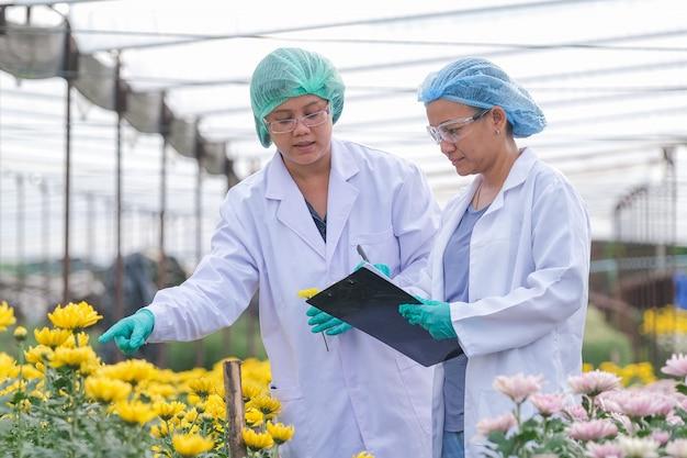 多色の花の前で白衣を持つ科学者の女性