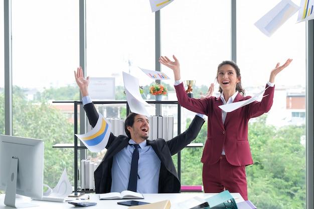 幸せなビジネスチームは、オフィスの会議室で成功した論文を投げることを祝う