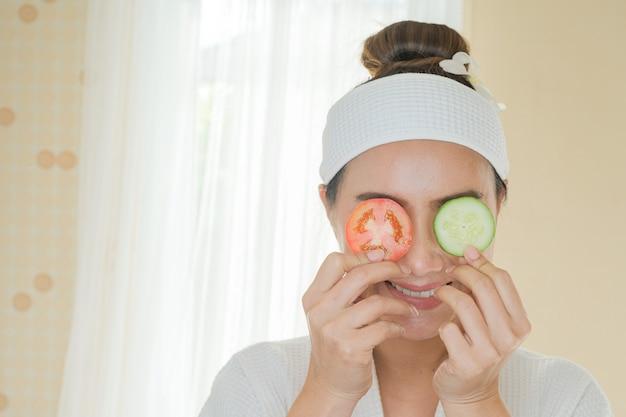 Красивая женщина с маска для лица, с огурцами и помидорами на глазу.