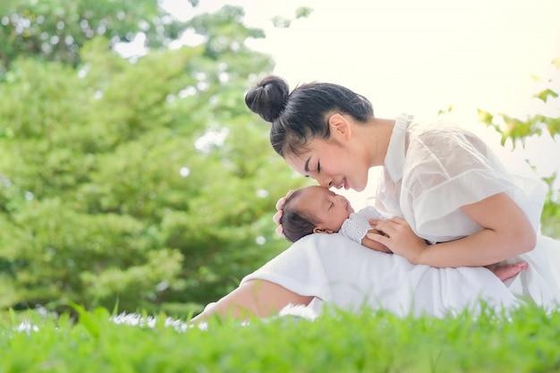 アジアの公園で美しい母親と赤ちゃん