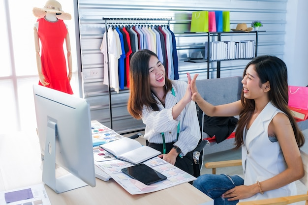 Азиатские женщины, которые работают модными дизайнерами и сшивают одежду на успешной работе.