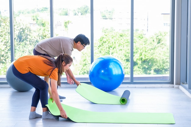 Пожилые мужчины и женщины укладывают коврики для йоги