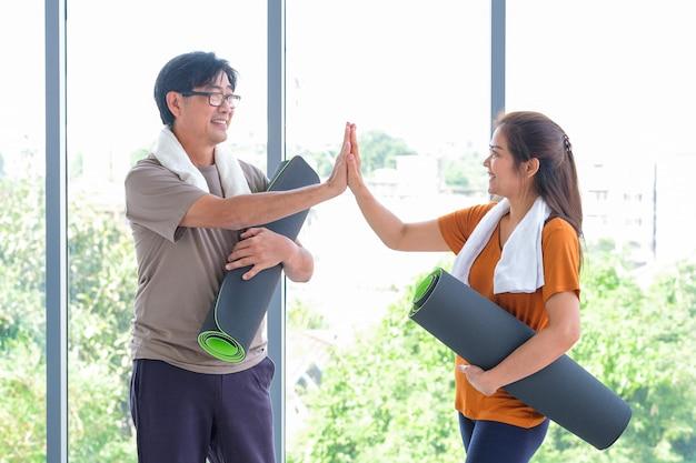 Зрелые мужчины держат в тренировочной студии коврики для йоги и дают женщине высокие пять