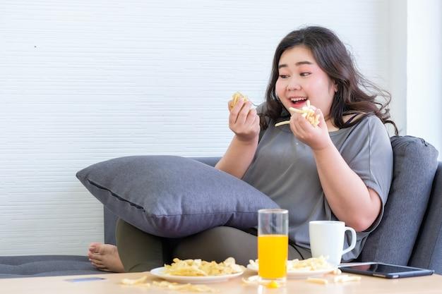 太ったアジアの女性は、部屋でフライドポテトを食べることを楽しんでいます。
