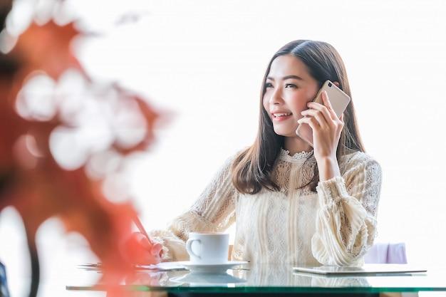 座って、働いて、コーヒーショップで電話で話しているアジアの実業家