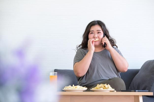 太ったアジアの女性は部屋でフライドポテトを食べることを楽しんでいます。