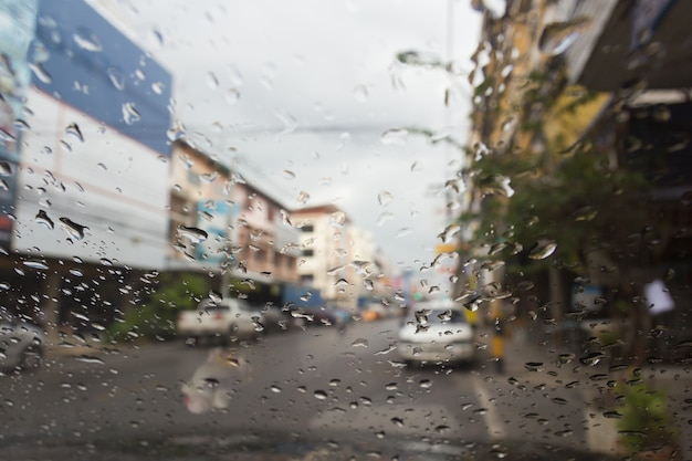 Вид дороги через окно автомобиля с каплями дождя