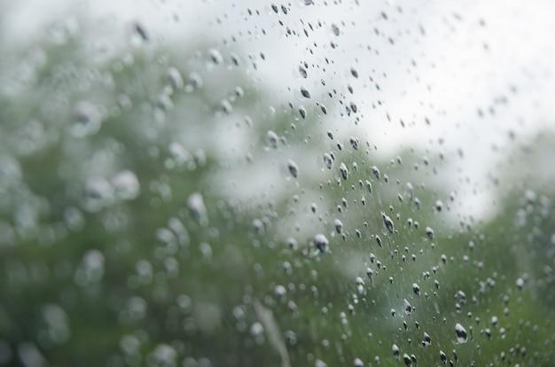 車の窓に雨が降る