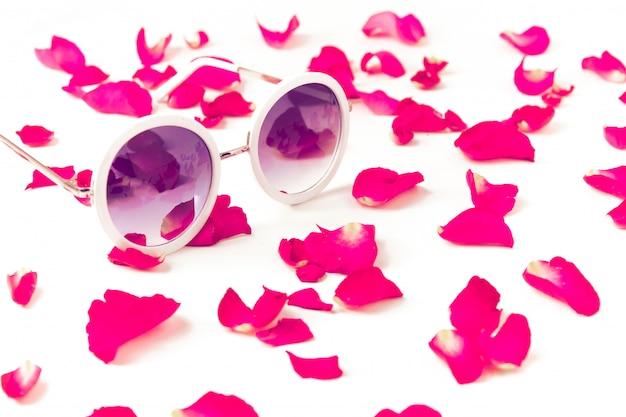 白地にピンクの赤いバラの花びらを持つ少女サングラスの美容ファッションリラックス夏のコンセプト