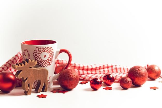 Блестящий шар с кофейной чашкой и игрушкой из дерева северного оленя и праздничное приветствие с рождественским украшением
