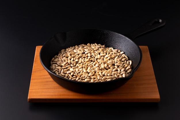 健康食品のコンセプト焼きヒマワリのバターフライパン鉄の有機ひまわりの種