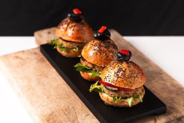 健康食品のコンセプトコピースペースを持つ黒いプラットに自家製ビーガンキノアハンバーガー