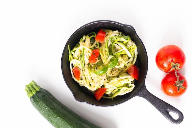健康食品のコンセプト自家製ギルテンフリーズッキーニ麺、鉄のフライパンでトマトのパスタ