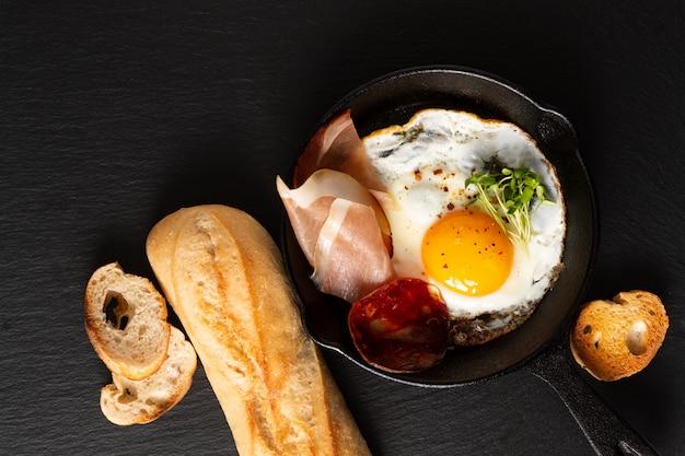 Жареное яйцо в сковороде сковороде с ростками льна и беконом с копией пространства