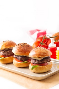 Концепция еды домашние говяжьи гамбургеры подают на квадратной тарелке
