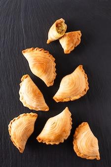 東南アジア起源食品コンセプト自家製チキンカレーパフコピースペースと黒いスレート石背景