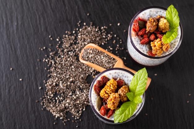 Концепция здорового питания семена чиа, молочный пудинг с годжи, белая шелковица и сухие семена в небольшом стакане на черном фоне из грифельной доски
