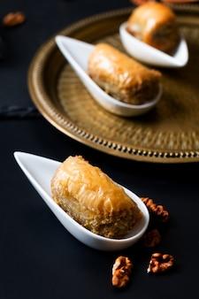 Концепция питания восточный арабский десерт пахлава грецкие орехи на черном грифельную доску