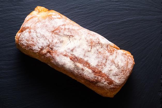 Продовольственная концепция вид сверху свежий домашний хлеб из органического хрустящего ремесленного хлеба на черном сланцевом камне