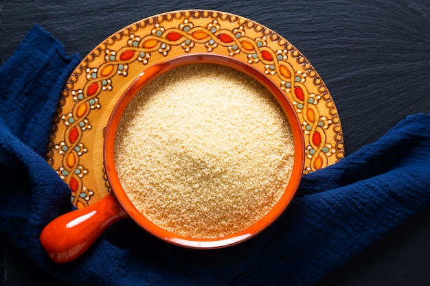 Пищевая концепция органического сырья кускус в миску апельсина