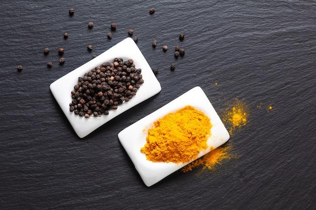 健康食品と代替医療成分コンセプトオーガニックブラックピーマンと正方形のセラミックカップのターメリックパウダー