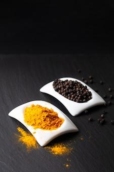 健康食品と代替医療成分概念有機ターメリックパウダーブラックピーマンと正方形のセラミックカップ
