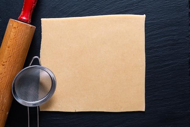Концепция еды домашнее сырое органическое тесто для слоеного теста для печеного пирога, печенья или пирогов на черной грифельной доске