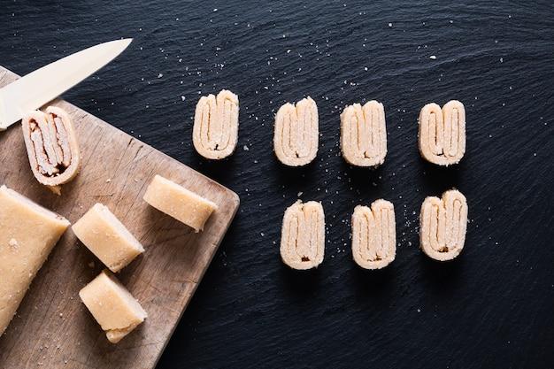 Концепция питания домашнее сырое органическое тесто для слоеного теста для французских пальмиеров, китайской выпечки бабочек или слоновьего теста на черной грифельной доске