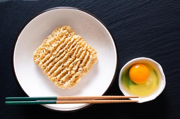 黒いスレートボードテーブルと生卵に不健康な乾燥麺
