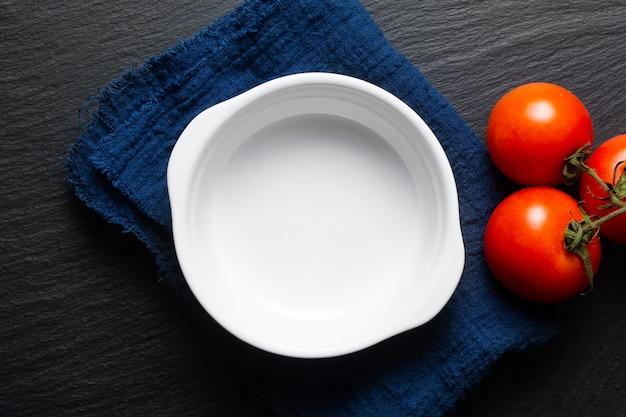 青いリネンナプキンとトマトの白いセラミック焼きボウル