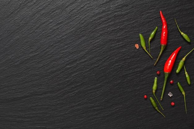 Пища пряный презентационный фон красный перец чили и зеленый чили на черной доске сланца