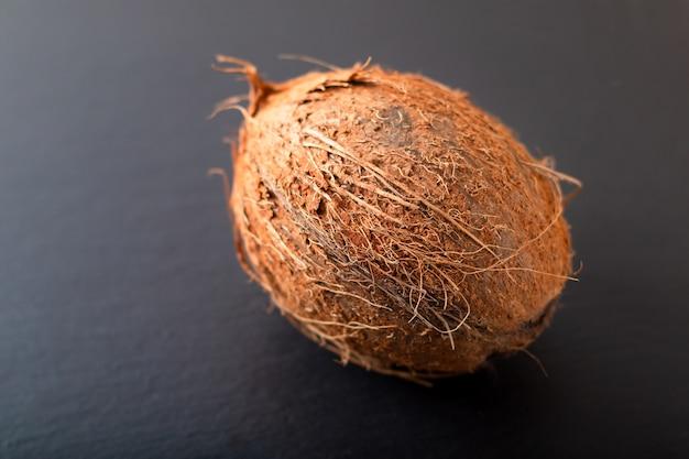 Весь один органический тропический кокосовый фрукт на черном сланце каменный фон с копией пространства
