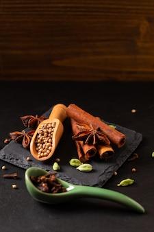 エキゾチックなハーブ食品のコンセプトコピーと黒のスレートの石のプレートに有機スパイスのミックス