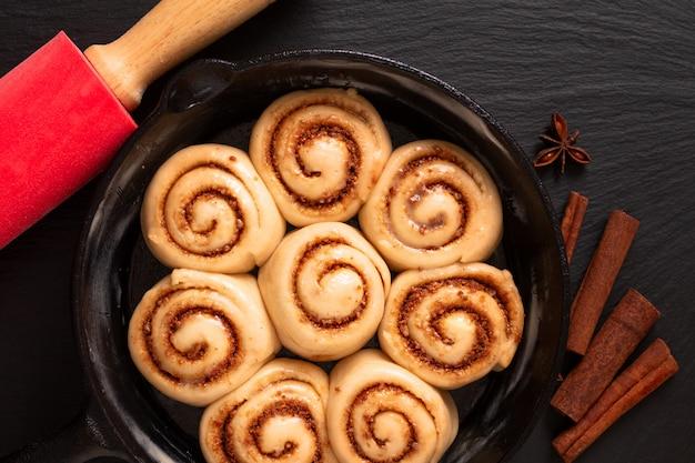 自家製シナモンロールの食品コンセプトふくらんでいるパン生地コピースペースを持つフライパン鋳鉄鍋で焼く前に調達