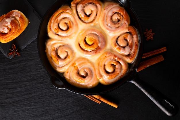 食品のコンセプト焼きたての自家製シナモンロールコピースペースを持つフライパン鋳鉄鍋