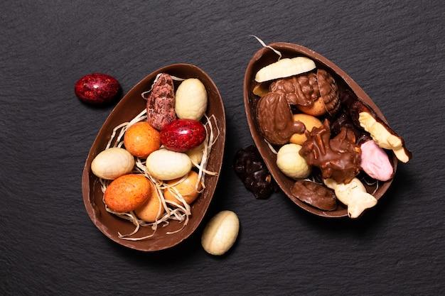 ホリデーフードのコンセプトコピースペースとカラフルなキャンディーとチョコレートのイースターエッグ