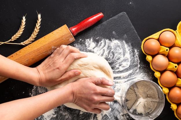 頭の上の食品準備の概念コピースペースと黒の背景にパン屋さん、ピザまたはパスタの生地を混練