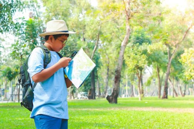 バックパックを運ぶ少年、地図を見る