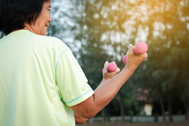 年配の女性はアジア人です。ピンクのダンベルを上げて、庭で健康のために運動します。