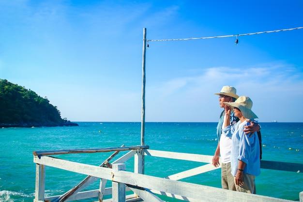 海で幸せなお互いを抱いて立っている高齢者のアジアのカップル。