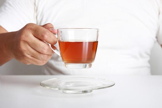 ホットティーのグラスを持っている脂肪男健康的なハーブ。