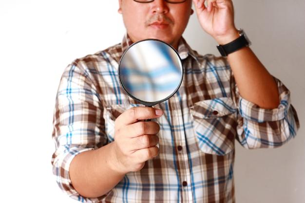 Мужчина держит увеличительное стекло