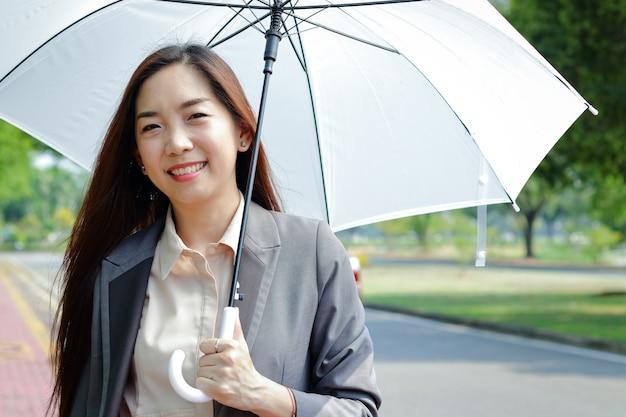 オフィスで働くアジアの少女彼女は暑い日傘をさしていた。