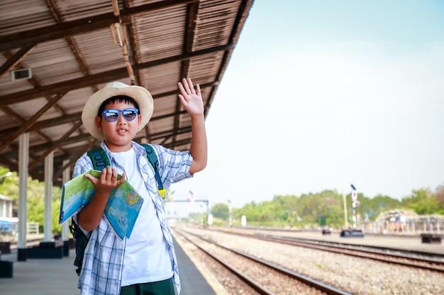 地図を持って少年が旅行する電車を待って立っています。