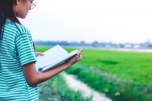 アジアの子どもたちは、勉強して学ぶために白い本を開きます。