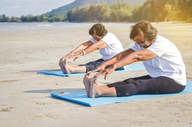 海沿いのビーチで運動している高齢者の女性新鮮な空気、強い体