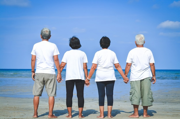 高齢者グループは立ち上がって、手を取り合って、白いシャツを着て、海を訪れました。